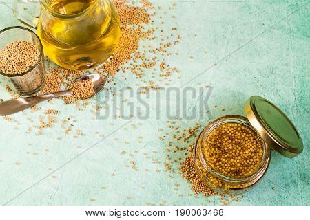 A jar with cooked mustard, a small glass with mustard seeds and a glass jug with mustard oil on a light background.