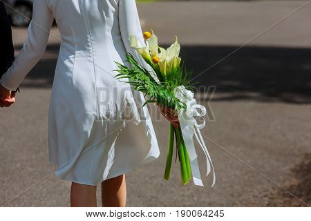 girl in a white dress with a bouquet of flowers and green against a background of green grass