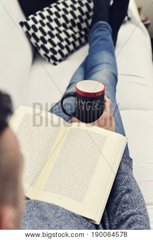 closeup of a young man reading a book with a cup of coffee in his hand with the text hygge, a danish and norwegian word for comfort or enjoy, which can be a whole philosophy of life