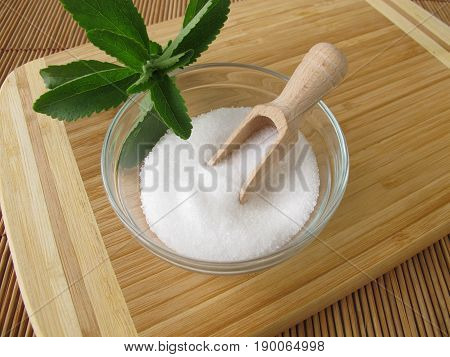 Stevia sugar free crystals in bowl an fresh stevia leaves