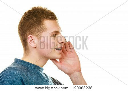 Spread the word theme gossip. Young man face profile with hand gesture speaking whispering isolated on white background