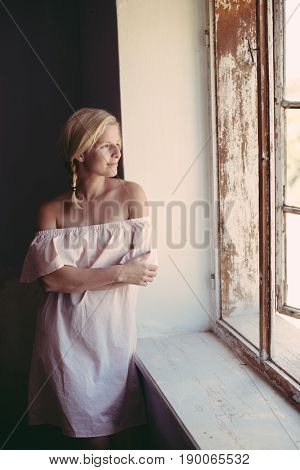 Cute blonde woman daydreaming at home, looking out window