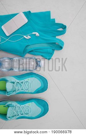 Flat Light Blue Athletic Shoes, A Bottle Of Water, A T-shirt And Headphones On A Gray Concrete Backg