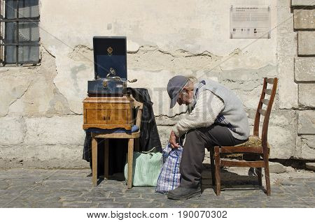 LVIV, UKRAINE - APRIL 10, 2017: Old age man with a gray beard sitting next to the antique gramophone.