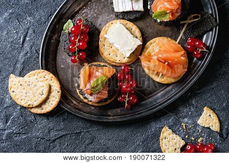 Stack of black charcoal and traditional crackers with smoked salmon, cream cheese, green salad and red currant berries on vintage metal tray over black stone background. Appetizer snack. Top view