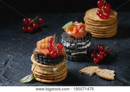 Stack of black wholegrain charcoal and traditional crackers with smoked salmon, cream cheese, green salad and red currant berries over black stone background. Appetizer snack. Space for text