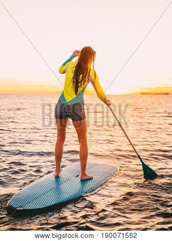 Attractive young woman stand up paddle surfing with beautiful sunset or sunrise colors