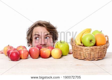 Man Looking To The Side With Crafty Smile Behind Apples