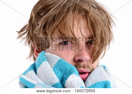 Man with tired and sleepy face expression and messy hair towels his chin isolated on white background close up. Morning shower time concept