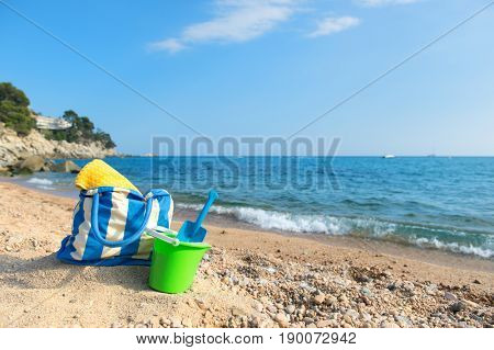 Vacation at the beach coast with beach bag and toys