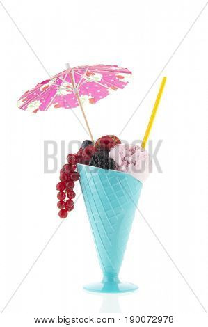 Blue glass with ice cream fruit of the forest isolated over white background