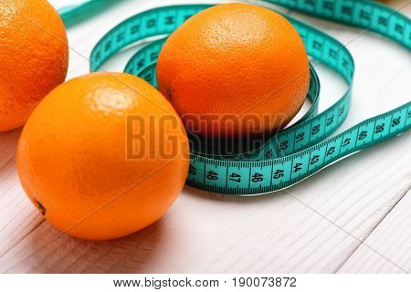 Oranges Lying In Circles Of Turquoise Measuring Tape