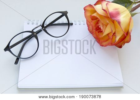 Notebook mock up for artwork with red and yellow rose and gasses . Top view. Place for text. Fresh flower