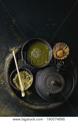 Green tea matcha powder and hot drink in black bowls standing with iron teapot, bamboo traditional tools spoon and whisk in terracotta tray over dark metal background. Top view with space