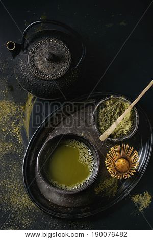 Green tea matcha powder and hot drink in black bowls standing with iron teapot, bamboo traditional tools spoon and whisk in vintage tray over dark metal background. Top view with space