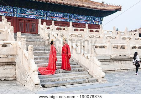 Couple In Red Dresses On Steps Of Hall For Worship