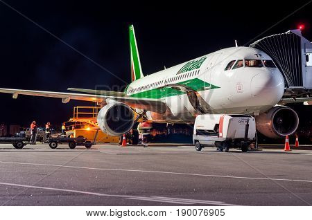KIEV, UKRAINE - MAY 2: Close view of Alitalia aircraft fuselage near the entering baggage door, at night. May 2, 2017