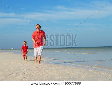 family beach vacation -father and son run at sea beach