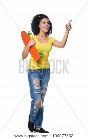 Full length surprised mixed race african american - caucasian female in distressed jeans with skateboard pointing to blank copy space