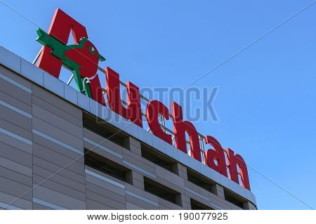 Krakow Poland - 03 June 2017: Sign of the Auchan hypermarket on the blue sky in a sunny day. Auchan is a French international distribution hypermarket network.