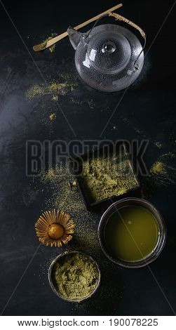 Green tea matcha powder and hot drink in black bowls and wood box standing with glass teapot, bamboo traditional tools spoon, whisk in terracotta tray over dark metal background. Top view with space
