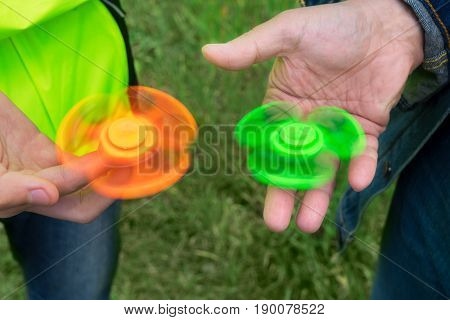 trendy fidget spinner - two persons holding spinning green and orange fidget spinners in hands, close up view