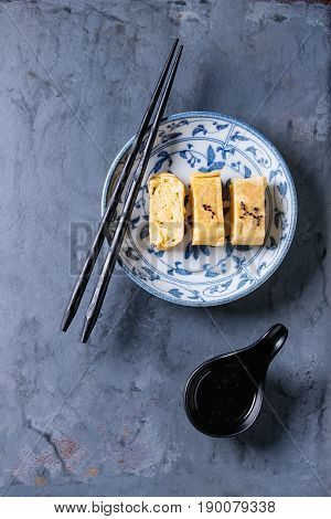 Japanese Rolled Omelette Tamagoyaki sliced with black seasame seeds and soy sauce, served in blue white ornate ceramic plate with chopsticks over blue gray metal background. Top view with space