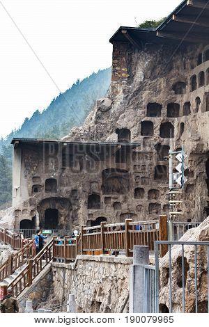 People Near Caves In Longmen Grottoes