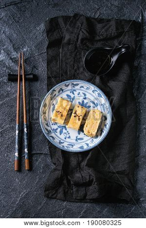 Japanese Rolled Omelette Tamagoyaki sliced with black seasame seeds and soy sauce, served in blue white ornate ceramic plate with chopsticks, textile over black stone background. Top view with space