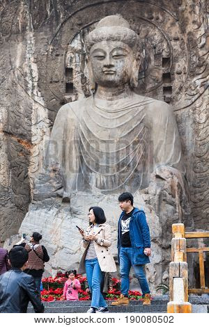 Tourists Near The Big Vairocana Statue In Longmen