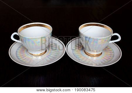 A pair of white iridescent tea cups and saucers