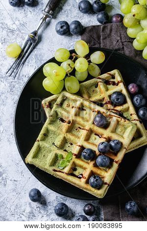 Homemade square green matcha belgian waffles on black plate with fresh ripe grapes, blueberries, mint, fork, textile napkin over gray texture background. Top view