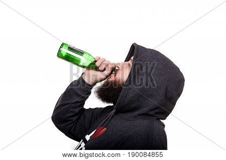 Alcoholic with a beard and mustache in the hood. Drinking beer from a bottle. Isolated on white background