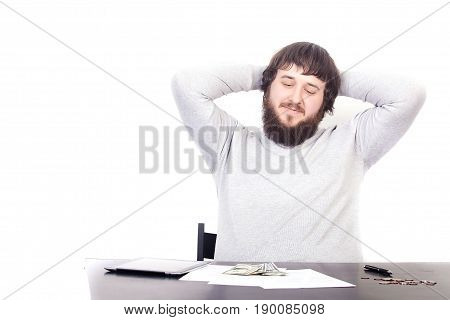 young attractive businessman happy and hectic looking at money on desk at office work sitting at desk satisfied and smiling relaxed leaning on chair isolated on white background.