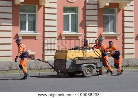 SAINT PETERSBURG, RUSSIA - MAY 26, 2017: Road workers - migrant workers wheeled the old compressor