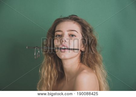 Girl With Metallic Nail In Mouth Showing Healthy Teeth