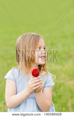 Little blond girl in a blue dress in the garden. Little girl laughing and having fun. A little girl is holding a basket with strawberries. Little girl eating strawberry