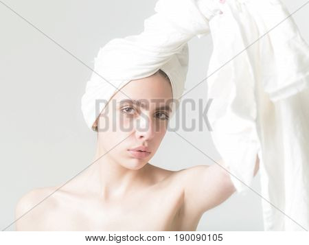 healthcare. Pretty woman or adorable girl with young pure face skin no make up unwinding white bath towel from head on grey background. Haircare spa natural beauty hygiene