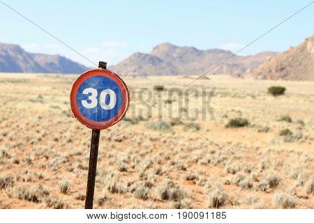 Vintage speed road sign made of an old barrel lid. Dry desert and grassland. 30 km sign.