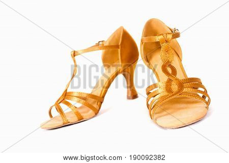 Golden shoes for latin american dances on white background.