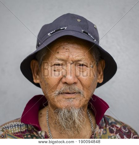 KATHMANDU NEPAL - SEPTEMBER 28 2016 : Portrait old men in traditional dress in street Pokhara Nepal