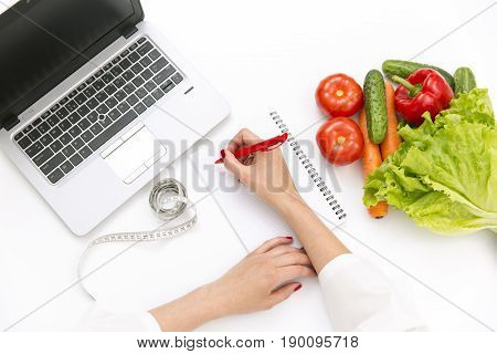 Vegetable diet nutrition or medicaments concept. Doctors hands writing diet plan ripe vegetable composition laptop and measuring tape on white background