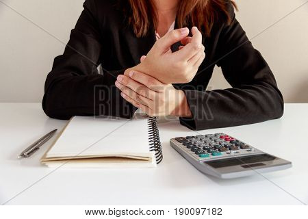 Businesswoman hands pain on desk office syndrome with notebook and calculator