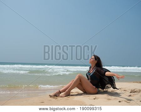 Portrait of a girl sitting on the beach with the sea or ocean