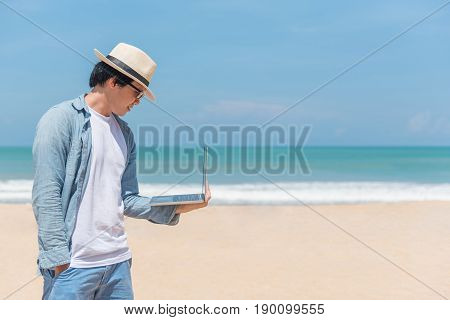 Young Asian happy man holding laptop on the beach working outdoor in summer season digital nomad lifestyle concepts
