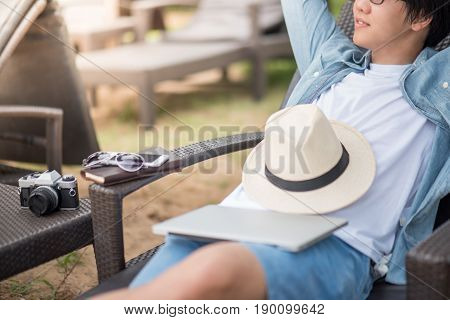 Young Asian man lying on bench near the beach with laptop notebook and camera fot outdoor working digital nomad lifestyle concepts