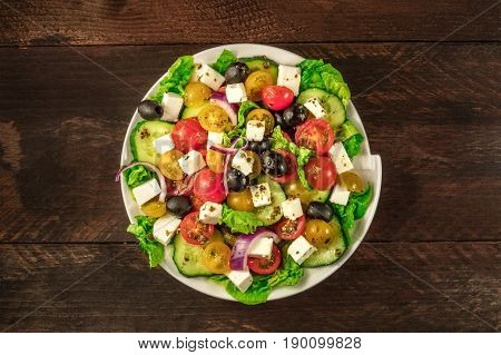 An overhead photo of a plate of Greek salad, with feta cheese, fresh vegetables, and olives, on a dark rustic texture with a place for text