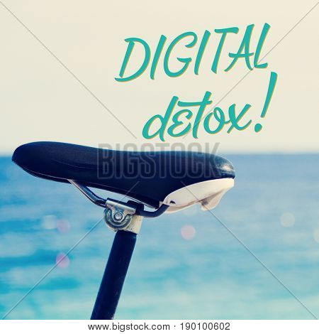 closeup of the saddle of a bicycle parked next to the sea and the text digital detox