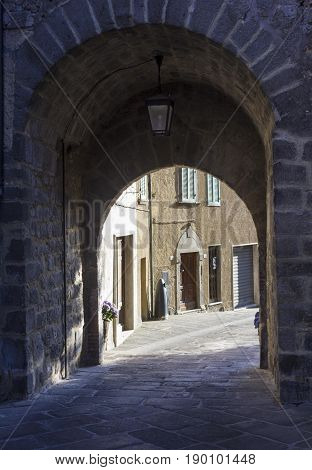 ABBADIA SAN SALVATORE, ITALY - JUNE 2 2017: historic city centre of the medieval city of Abbadia San Salvatore in Tuscany Italy. Archway to the fortress