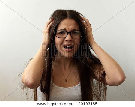 Shocked pretty young woman with hands on head thinking and having problems standing against white background.